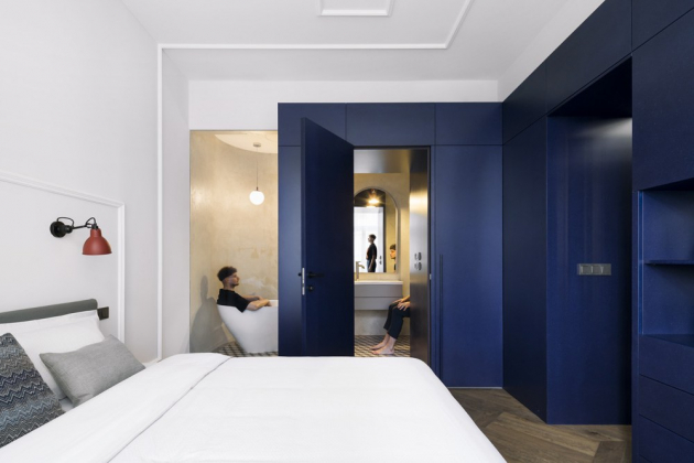 Lišty na stropech plynule přecházejí na zdi, kde fungují například jako rám pro budoucí čelo postele nebo v obytném prostoru vymezují místo pro osazení TV. Vestavný nábytek na míru je i součástí ložnice