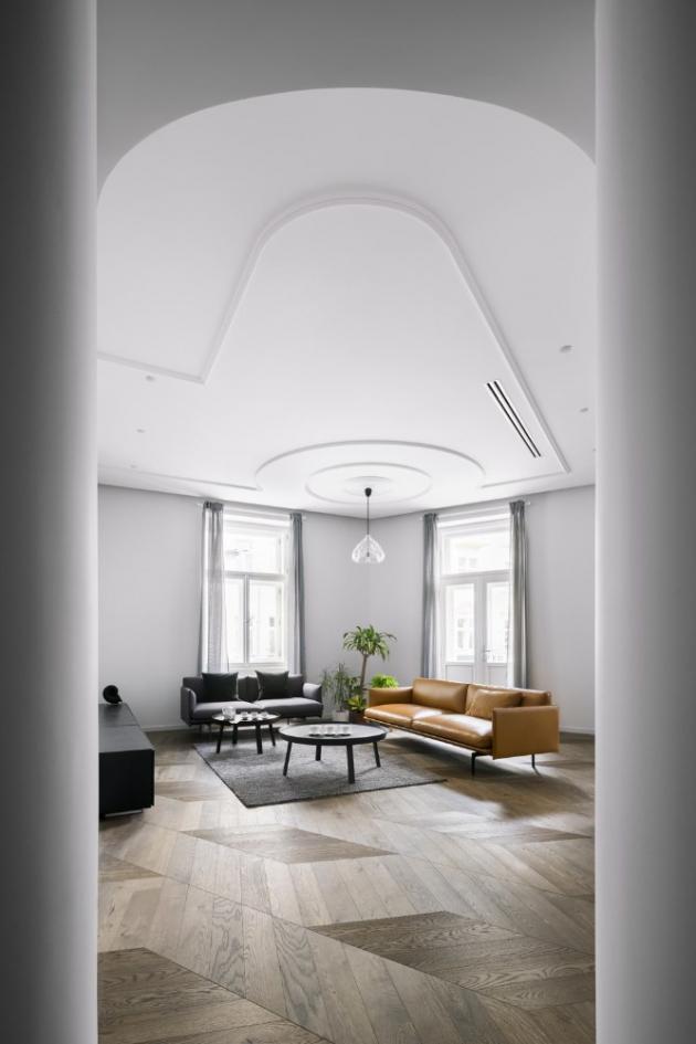 S tvaroslovím lišt si architekti pohrávají také na stropě, kde se do sebe zakusují kružnice kolem lustrů. Lištami jsou též rámována v podstatě velmi jednoduchá přisazená svítidla, která tím získávají luxusnější vzhled. Podlahu místností tvoří atypicky kladená dřevěná podlaha z dubových parket. Nábytek dodala společnost Stockist