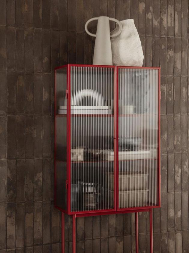 Uhlazený a matný kov versus vlnité sklo. Subtilní konstrukce jako pevná opora křehké výplni. Transparentní plochy jsou lícovány křiklavým odstínem poppy red.