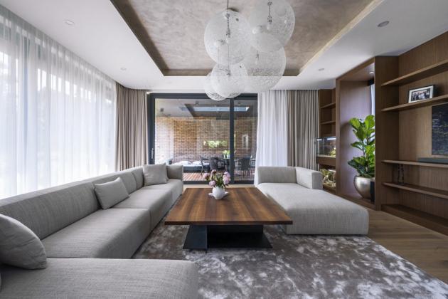 Obývací zóna plynule navazuje na rozlehlou terasu, která je shora krytá stropem patra. Díky zastřešení bylo možné na terase vybudovat venkovní kuchyň s grilem a velkorysé sezení