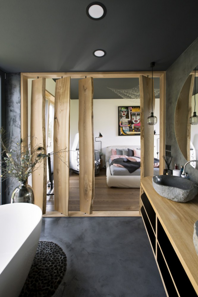 Koupelna je od ložnice oddělena pouze příčkou z vertikálně usazených otočných fošen z modřínového dřeva. Cementovou stěrku na stěnách a podlaze doplňují říční oblázky použité pod volně stojící vanou a uvnitř sprchového koutu. Z přírodního kamene jsou také umyvadla