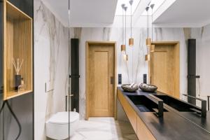 Posunutím dveří se uvolnil roh místnosti, takže umyvadlová skříňka vyplňuje celou délku přilehlé stěny. Světlost prostoru zvyšuje velkoplošné zrcadlo, umělý světlík i závěsná svítidla