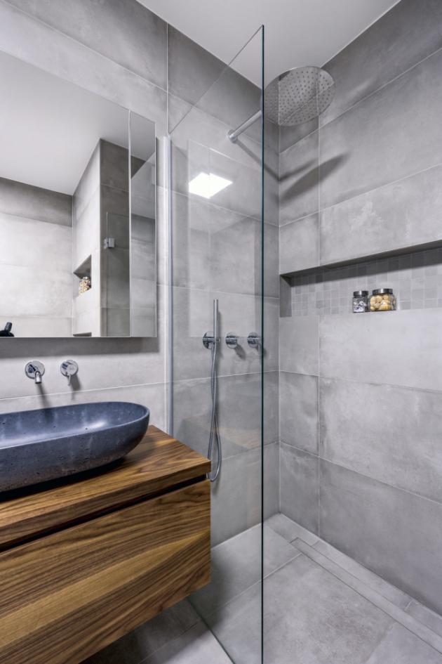 Prostorný sprchový kout typu walk-in je vybavený ruční i hlavovou sprchou. K odkládání hygienických potřeb slouží nika osvětlená LED páskem