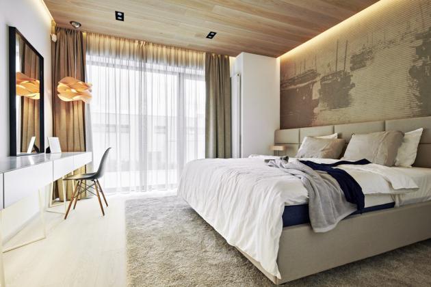 Čalouněná postel je zhotovena na míru. Za ní je vinylová tapeta Boats. Podle autorského návrhu je vyroben i toaletní stolek s kovovou podnoží, kde je umístěno zrcadlo v tenkém černém kovovém rámu. Je nasvícený zavěšeným svítidlem (LZF) a doplněn černou židlí Eames DSW (Vitra)