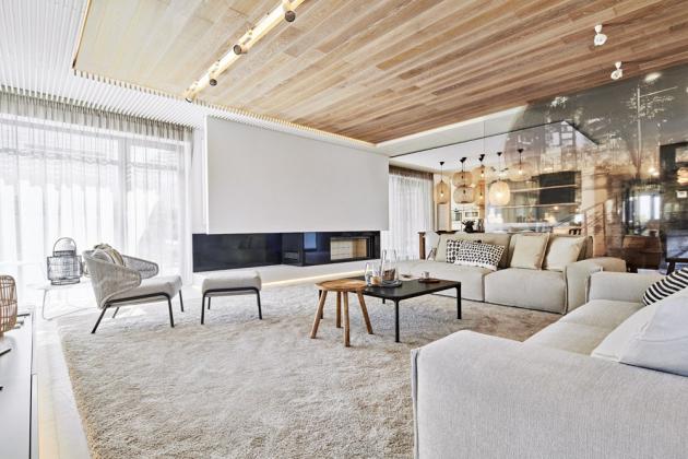 Podlahu obývacího pokoje kryje velkoformátový koberec Lano Pearl. Je zde umístěno křeslo Radius s podnožkou, dřevěný kulatý stolek Love a černý čtvercový stolek Slim