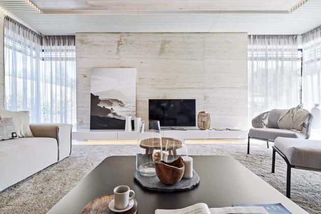 Stěny v obývacím pokoji jsou obložené přírodním travertinem. Na míru z MDF desky je zhotovený bílý nábytek pod TV