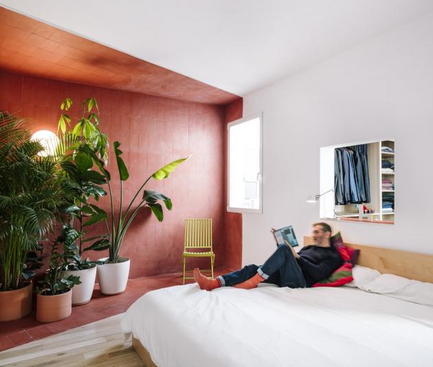 Součástí minimalistické ložnice je i červeně vyznačená odpočinková zóna, ve které si majitel vybudoval malou soukromou džungli