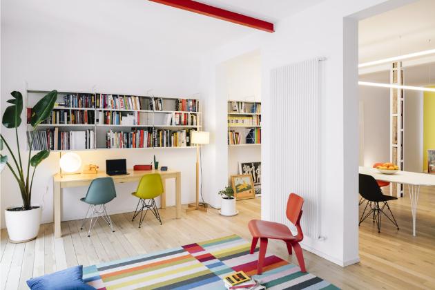 Pracovní část s bohatou knihovnou je od té obývací a odpočinkové oddělena jen velmi ležérně – pestrým kobercem