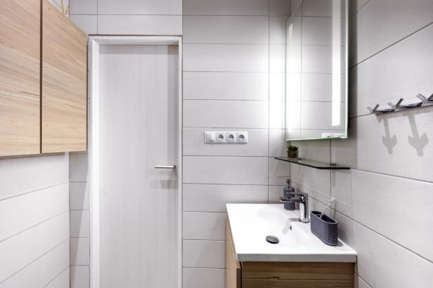 Aby zůstal u umyvadla vedle sprchového koutu manipulační prostor, zvolili majitelé užší typ umyvadlové skříňky z kolekce Mio-N s šířkou 44,5 cm, typ s dřevodekorem javoru