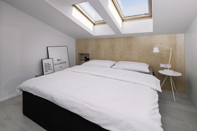 Také čelo postele je zhotoveno na míru z přírodní světlé překližky. Zahrnuje malou niku nahrazující noční stolek s integrovaným spínačem a zásuvkami. Na ložnici navazující pracovnu lze časem využít také jako místnost určenou pro jiné účely, kterou je možné snadno oddělit bez nutnosti stavebních úprav. Do původně poměrně malé koupelny se posunem příčky vešla vana i sprchový kout, umyvadlo, klozet i prostor pro umístění pračky. Nechybí ani nezbytné úložné prostory.