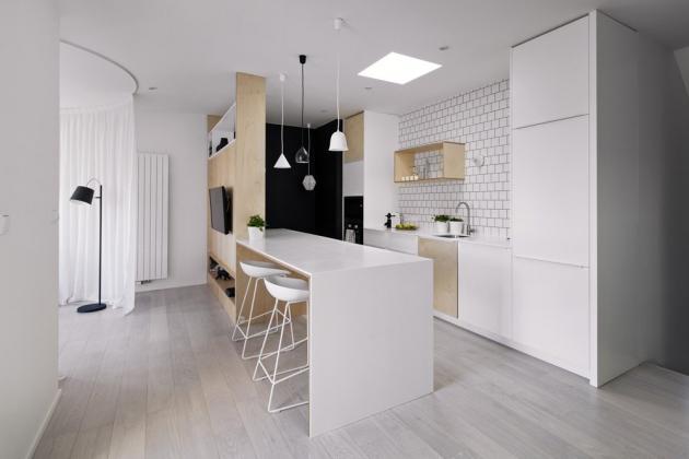 Vzhled světlého interiéru podpořila podlaha z běleného dubu i nábytek na míru navržený podle autorského návrhu studia SMLXL a zhotovený v kombinaci přírodní překližky a bílého laku. Bílé jsou i vysoké barové židle (HAY). Ostře kontrastní tmavá místa v bytě tvoří jen černé stěny povrchově upravené černým tabulovým nátěrem. V barevném souladu jsou použita i závěsná svítidla (Norr11) nad barovým stolem. Velký kuchyňský ostrůvek přechází do prostoru jako bar či jídelní stůl. Dvě křesílka (Condesa – OKdesign) umístěná v nice s výhledem do dvora prakticky poslouží také při sledování televize.