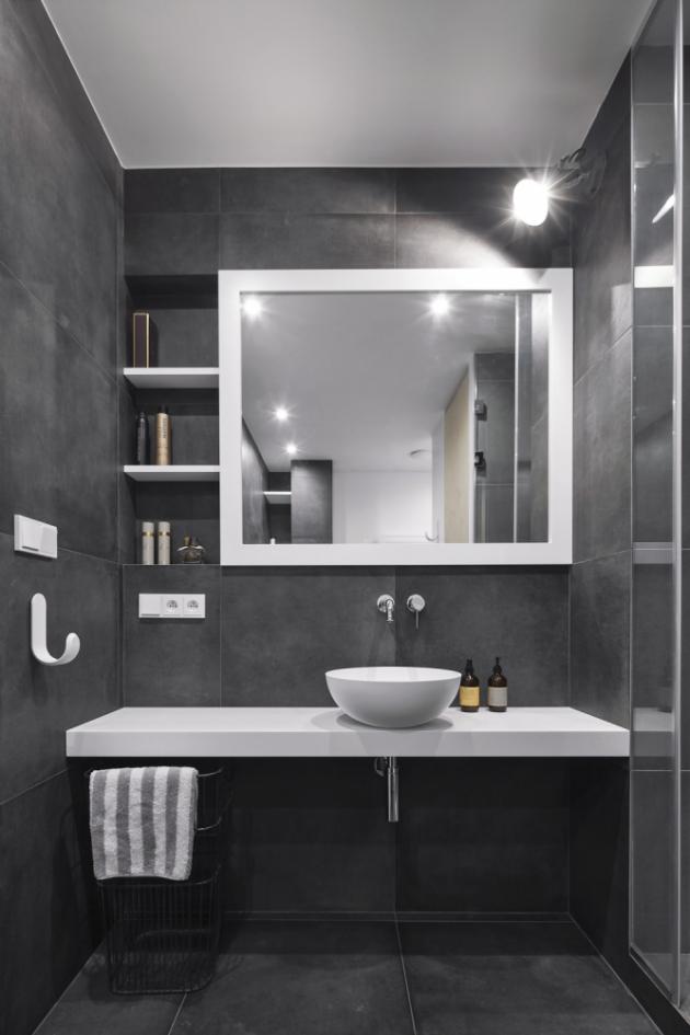 Tmavá keramická podlaha i obklady sahající až ke stropu umocňují intimitu koupelny. Tím, že nechybí ani vana, tak i její maximálně relaxační účel