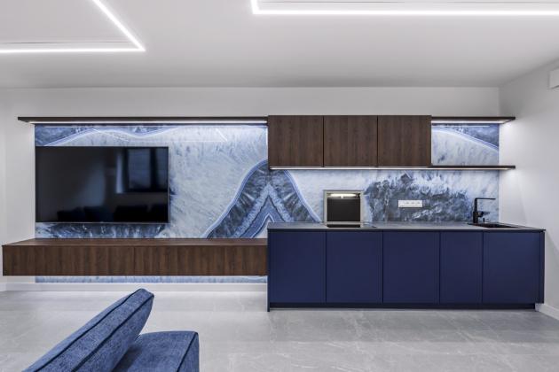 Na obložení stěny byly použité obklady Agate Blue (Gardenia) s formátem 160 × 320 cm. Sestavu opticky lemuje prosvětlená horní policová linka, která navazuje na horizontální linii nad vstupními dveřmi, WWW.JNINTERIER.CZ, WWW.ARGINOVA.CZ