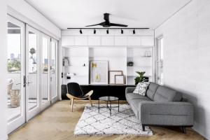Obývací prostor v prvním patře tvoří plynulý přechod ze soukromých prostor rodiny majitele do těch sdílených v přístavbě. Díky využití světlých barev je velmi vzdušný, přírodní dekor dřeva jej pak naopak příjemně uzemňuje a prohřívá.