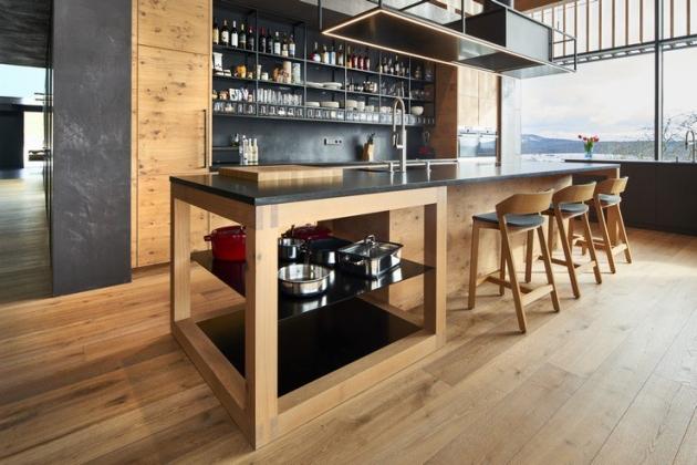 Ve druhém chaletu se pak nachází společenská část domu, která skýtá obývací pokoj s kuchyní včetně jídelny a kde se opět skvěle doplňují dřevěné prvky s moderní cementovou stěrkou Imitace betonu®, která reálně imituje betonové monolity.