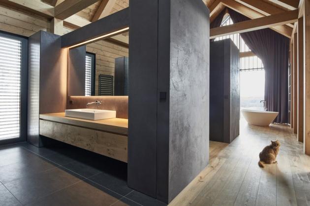 Je zřejmé, že byl kladen veliký důraz na pečlivý výběr materiálů a esteticky jednoduchá řešení, které se odrážejí v čistotě celého domu. Právě proto byla v chaletu, kde se nachází privátní část v podobě ložnice se šatnou a koupelnou, použita voděodolná stěrka Betonepox®, která se dokáže přizpůsobit jakémukoli odstínu a její aplikace je možná i na koupelnový nábytek.