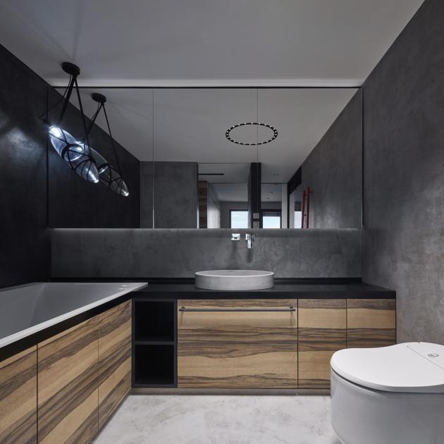 Osvětlení je v celém bytě až na pár výjimek vyřešeno vestavnými a místy přisazenými bodovými svítidly. Společně s čistými liniemi nábytku řešeného na míru a v kontextu elegantní barevnosti i odvážných detailů interiér evokuje luxusní hotel.
