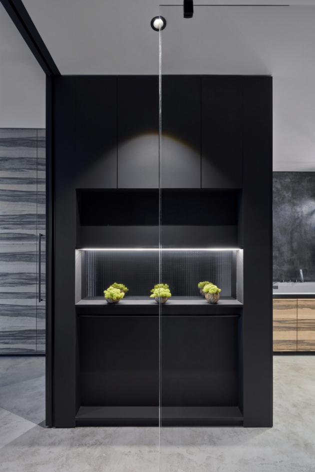 Otevřený prostor výrazně sjednocuje šedá litá podlaha použitá na celé ploše bytu. Funkční zóny bytu na sebe plynule navazují, ale v případě potřeby je lze rozdělit posuvnými skleněnými dveřmi.