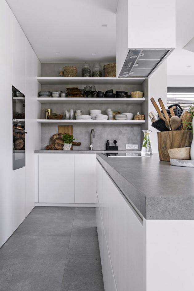 V obytném prostoru nelze přehlédnout důmyslnou práci s efektní geometrií. Spirála schodů je podpořena kruhovým půdorysem kamen, motiv kruhu je zopakován i v podobě velmi subtilních konferenčních stolků z lakovaného kovu a černě lakované dýhy. Sestava kuchyňského nábytku je vyrobena na míru z lakované MDF desky a působivě střídá minimalisticky řešené úložné skříňky s otevřenými vzdušnými policemi. Vícedílná čalouněná pohovka Pixel (Saba) umožňuje díky odnímatelným opěrákům mimořádnou variabilitu užití. Lehkost přírodních odstínů podtrhuje akcent černé barvy, který tu umocňují také subtilní kožená křesla (Light and Living) a kovová svítidla.