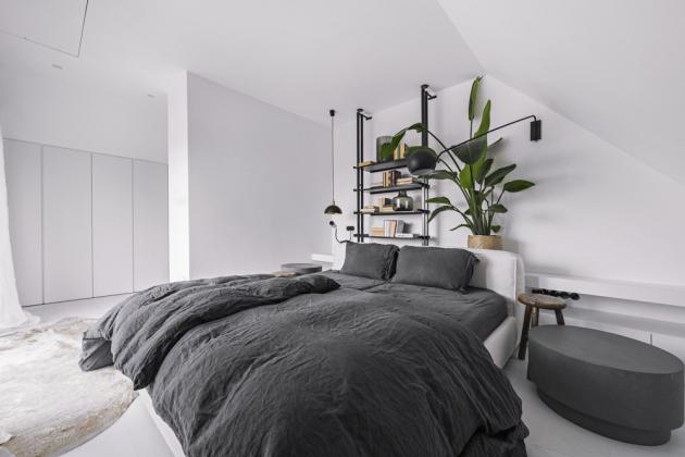 Ústřední bodem ložnice v patře je čalouněné lůžko (Flexteam) a černě lakovaný kovový regál, zhotovený na míru podle návrhu architekta Martina Franka. Doplňují ho stolky z jilmového dřeva a betonový odkládací stolek (Pomax), skříně jsou vyrobeny z bíle lakované MDF desky. Zelené rostliny byly pro paní domu výzvou. I přes její obavy se jim ale daří a oživují interiér dalším barevným akcentem. Ze zvoleného stylu interiéru nevybočuje ani pracovna v přízemí domu, snad jen hojnějším užitím černé barvy. Vstupní prostor domu je osazen velkým, částečně do kruhu řezaným zrcadlem, jilmovou stoličkou, kovovým odkládacím stolkem a taburetem (Hübsch).