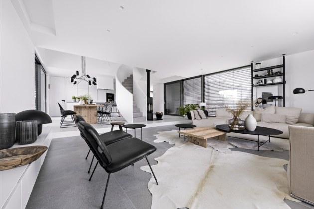 Podlahu sníženého patra obývacího pokoje kryje velkoformátová dlažba, připomínající betonovou stěrku, a vyšší část s jídelnou bíle olejované jasanové dřevo.