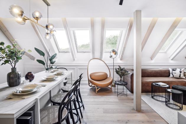 Díky dostatečnému množství střešních oken a všudypřítomnému využití světlých barevných tonů působí byt velmi vzdušným dojmem. Abstraktní obraz z dílny Lukáše Musila dodává prostoru moderní energii a specifický ráz