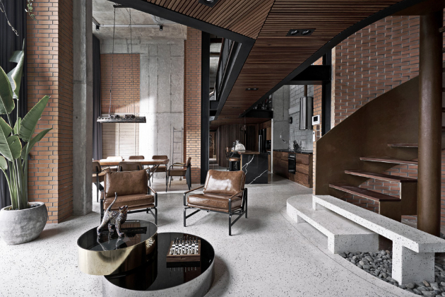 Hlavní obývací místnost je zcela charakteristická úctyhodně vysokým stropem a striktním využitím industriálních materiálů. V kontrastu k jejich surovosti stojí jen vzrostlé pokojové rostliny.