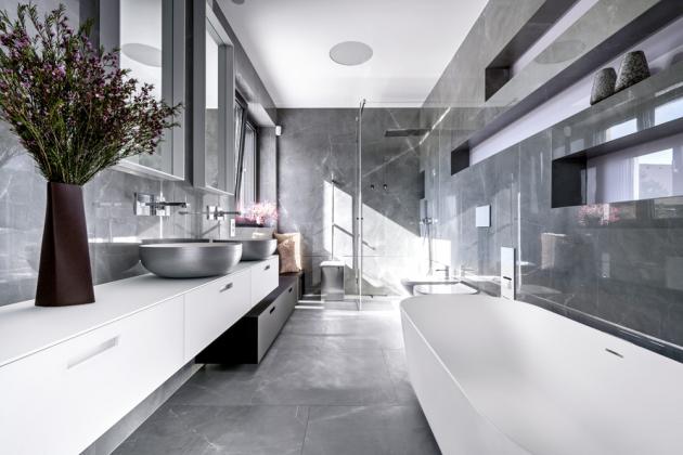 V obou koupelnách jsou použité baterie značky Gessi. Nábytek včetně zrcadel je od společnosti Casabath, která nabízí širokou škálu rozměrů i materiálových řešení. Ve výšce vany je patrná broušené nerezová lišta, díky které nevnímáme horizontální spáru obkladů. Na stěnách a na podlaze jsou velkoformátové matné a lesklé dlaždice Lea s dekorem šedého mramoru.