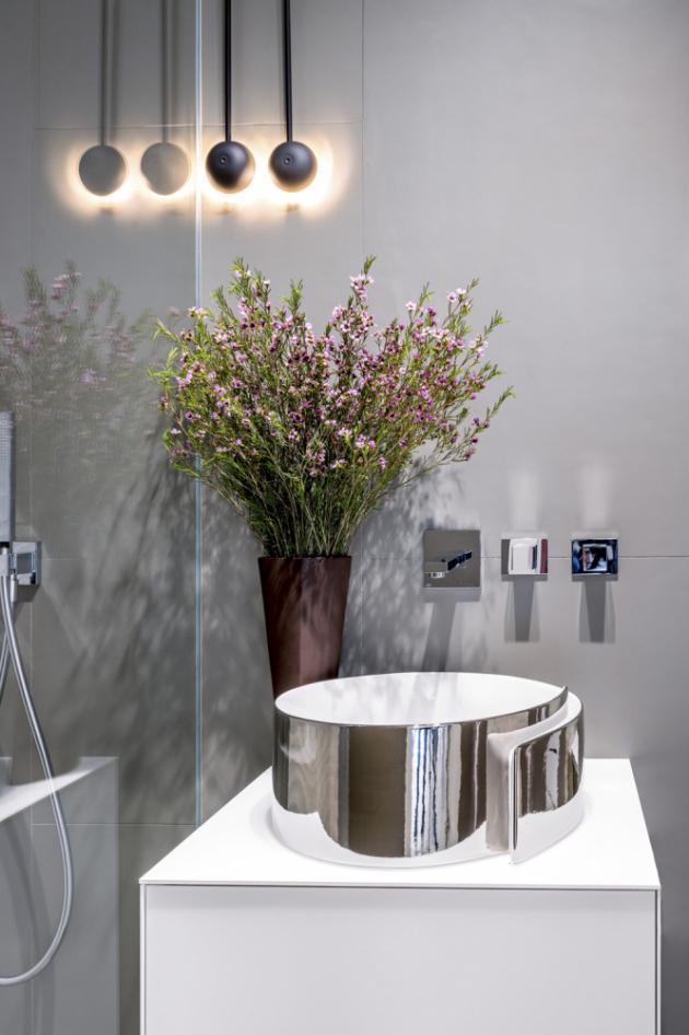 Sprchový kout odděluje pevná sprchová zástěna bez rámu. Na stěnách a na podlaze je podlouhlý, nepravidelně položený obklad 60 x 120 cm od značky Fondovale, na předstěně je obklad se 3D dekorem od Porcelanosy. Umyvadlo Flaminia v provedení bílá a platina je položené na skříňce Casabath se dvěma zásuvkami s bezúchytovým otvíráním. Toaleta Flaminia typu rimless je doplněna vzdáleným splachováním a podomítkovým modulem Emco.