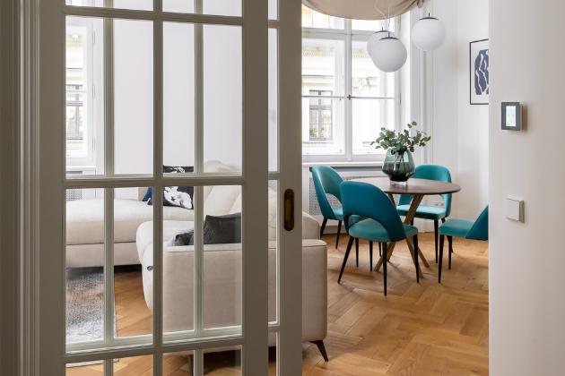 Dřevěné parkety si zaslouží vyniknout, a co si budeme povídat, v klasickém interiéru mají své nezpochybnitelné místo. Spektrum odstínů béžové si s nimi rozumí na jedničku, fungují ale i v kombinaci se zářivě barevnými detaily, které v tomto případě představují sametem čalouněné tyrkysové židle.