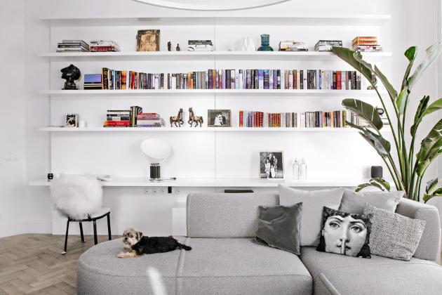 Kuchyň, vybavenou spotřebiči Miele a vyrobenou ze světoznámého kararského mramoru, je možné nechat skrýt za bílými uzavíratelnými panely. Dokonale tak splyne s ostatním vestavným nábytkem. Otevřená knihovna nabízí dostatek místa, je vyrobena přes celou stěnu. Sofa v arkýři bylo zhotoveno na míru. S vyšším stolkem a židlemi může suplovat jídelnu. V prostoru nelze přehlédnout atraktivní dekorace Fornasetti.
