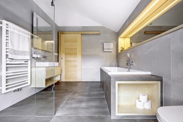 Původně plánovaný bidet uvolnil místo pro prostornou vanu Varia (Santech). Na boku jejího obložení vznikla praktická polička, která funguje jako zásobník toaletního papíru. Z pohledu od vstupu je částečně zakrytá toaleta Gap (Roca). Sprchový kout byl zhotoven na zakázku sklenářstvím JV Glass. Na dosoušení ručníků slouží radiátor Avento Frame (PHM).