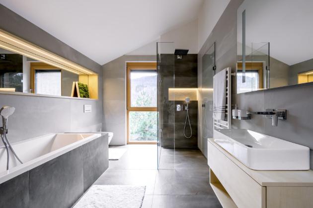 Výrazným prvkem koupelny jsou niky s osvětlením. Na skříňce zhotovené na zakázku je umyvadlo Sanlife (Sanindusa), baterie Metropol (Hansgrohe) a doplňky z řady Kibo (Nimco). Stěnu sprchového koutu odlišují tmavší dlaždice, které jsou v ostatních částech použité jen na podlaze. Původní návrh živého mechového obložení niky nad vanou se z praktických důvodů nerealizoval, jako vzpomínka tu ale zůstala mechová ilustrace.