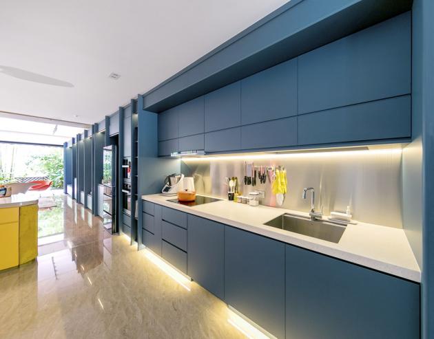 Kontrast použitých materiálů vytváří nečekaně harmonický celek. Absolutní dominantou přízemí je rozměrný policový systém v modré barvě, kterému zdatně sekunduje žlutý kuchyňský ostrůvek s pohledovou stranou z litého betonu.