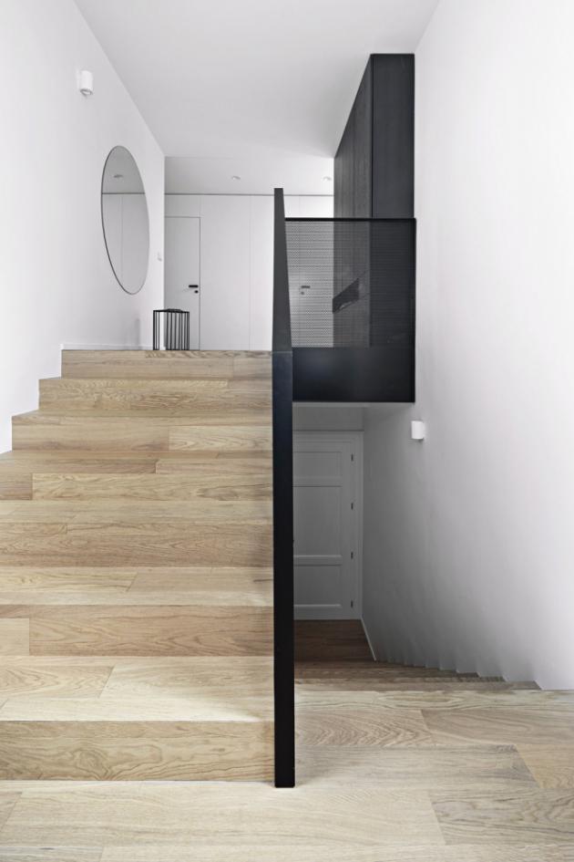 Zábradlí schodiště je vyrobeno z černého perforovaného kovu, který propouští jemné rozptýlené světlo. Úzký vstupní prostor opticky odlehčují protilehlá velká okna, umístěná přímo pod vysokým stropem, nad schodištěm stejně dobře slouží kulaté zrcadlo.