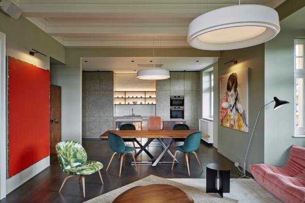 Tradiční dřevěné podlahy se střídají s barevně různorodou cementovou dlažbou. Tvoří tak skvělý základ pro výraznou barevnost a eklektickou atmosféru – té architekti dosáhli kombinací výrazných materiálů a stylů. Konkrétní odstíny přitom volili s ohledem na moderní obrazy, které majitelé od začátku plánovali v interiéru použít.