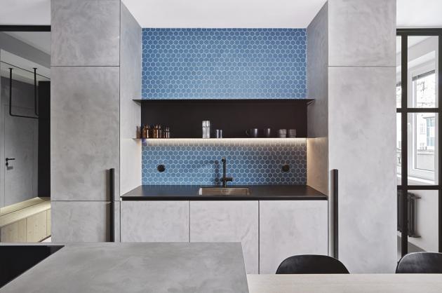 Zásadní bylo otevřít hlavní místnost, a ukázat tak největší prostor bytu v plné kráse. Barevnost interiéru je střídmá, neutrální. Proto do ní chtěli tvůrci vnést trochu rafinovanosti v podobě modrého kontrastu. Otevřený prostor ozvláštňuje kompozice svítidel Volta (Estiluz). Černou barvu v kuchyni podporuje kuchyňská baterie (Grohe) v černé barvě a spotřebiče AEG a Electrolux.
