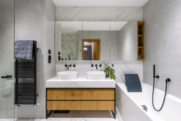 Vodovodní baterie chtěla Jana Collins stoprocentně černé. Vybrala si sérii Tara od značky Dornbracht, která perfektně ladí s betonovou stěrkou a velkoformátovou dlažbou v dekoru mramoru. Protože byt byl původní dispozicí klasicky řešený developerem, nebyla koupelna příliš velká. To se vyřešilo posunutím příčky do chodby a propojením koupelny s toaletou. Díky tomu se vešel do koupelny nejen velký sprchový kout, ale i vana. Navíc v koupelně nenajdete ani pračku se sušičkou. Ty designérka, jak sama říká, ráda z koupelen uklízí raději někam, kde nejsou vidět, a stejně je tomu i v její vlastní koupelně.