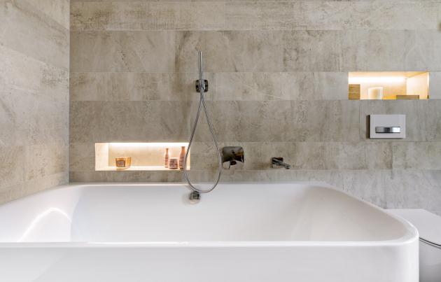 Jednolitost ploch narušuje jen minimum věcí. Sprchová a vanová baterie jsou podomítkové, sprchový kout je bez vaničky, pouze s nenápadným odtokovým žlabem. Díky tomu vypadá koupelna opticky větší