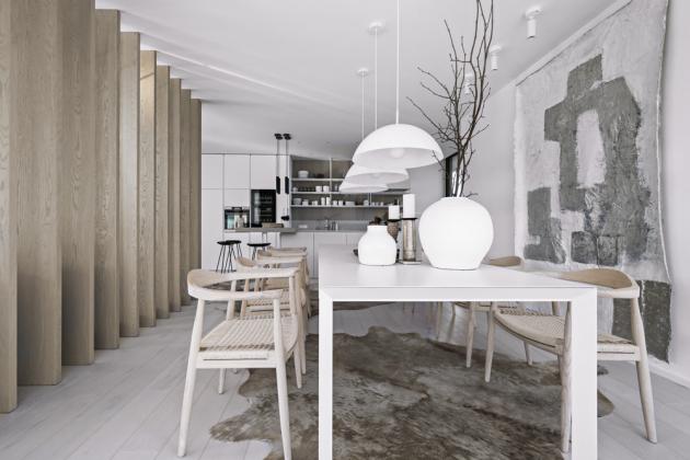 Prostor členící a nosné prvky domu skrývající lamely posloužily k uchycení nástěnné lampy s dlouhým ramenem (Flos 265, Stockist). Sestavu sedacího nábytku doplnila dvě subtilní křesílka (Menu, Stockist) z lakovaného kovu a kůže. Barový stůl vycházející z prodlouženého ostrůvku doplňují černá závěsná svítidla (Wever Ducré) a černé barové stoličky. Nejen prostor jídelny s velkým rozkládacím stolem (Pianca) o rozměrech 3 × 1 m nabízí dokonalé místo k setkávání rozvětvené vícegenerační rodiny. Lakovaný hliníkový stůl je doplněn židlemi z masivního dřeva s provazovým výpletem a závěsnými svítidly (HK Living).