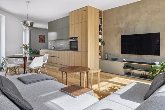 Téměř veškerý nábytek v interiéru je zhotovený na zakázku. Kombinuje dubovou dýhu a matný lak, který barevně ladí se stěrkou na stěnách. Sedací souprava je opatřena praktickými opěradly, s nimiž je možné hýbat a různě je posunovat. Společně se stolky ji majitelé pořídili u prodejce Situs