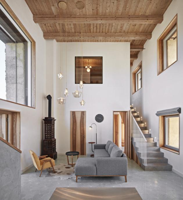 Hlavní obytný prostor převýšený přes dvě patra zahrnuje obývací část s kachlovými kamny a kuchyni s jídelním stolem. Okna striktně nenásledují otvory původního stavení z důvodu větších nároků na přirozené světlo, výhledy a vstupy do krajiny.