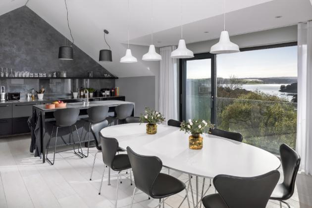 Modulární kuchyň V1 (Vipp) z kovu s černou práškovou barvou doplňují dvě černá závěsná svítidla a rychlovarná konvice téže značky. Jídelní stůl obklopuje osm židlí Series 7 (Fritz Hansen) celopolstrovaných černou kůží. Paletou tichých barev, jako je bílá, černá, antracitová a šedá, použitých v hlavním pokoji intenzivně zní oranžový akcent a dodává prostoru dynamiku.