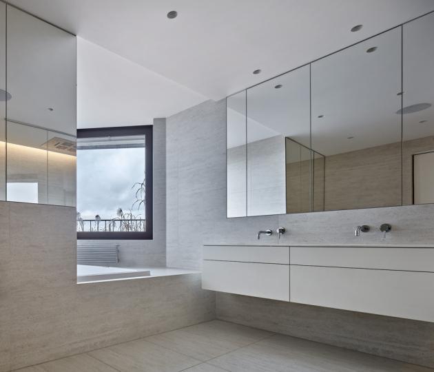 Koupelny prošly kompletní přeměnou. V jedné z nich vzniklo vyvýšené pódium s vanou, která nabízí výhled až na Pražský hrad. Součástí této koupelny je také velký sprchový kout s vestavnou wellness sprchovou hlavicí. Obklady a dlažbu z velkoformátové slinuté keramiky, evokující efekt travertinu, střídá v dětské koupelně skleněná mozaika a šedá dlažba.