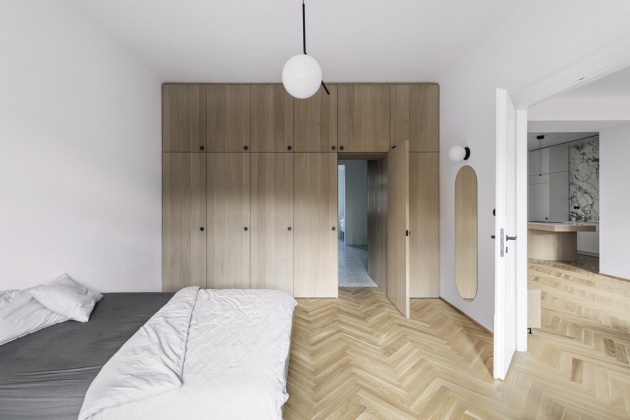 Rafinované vstupy do přilehlých prostor průnikem skříněmi skýtá ložnice i dětský pokoj. Postel v dětském pokoji je navržená na míru. Místnost nabídla i dostatek prostoru k umístění relaxačního křesla s podnožkou (HAY). Charakteristická modrobílá kostka prozrazuje legendární lůžko (Hästens) švédské provenience, které najdete v ložnici v doprovodu nástěnných lampiček Vipp 524 (Vipp) z černě lakovaného hliníku.