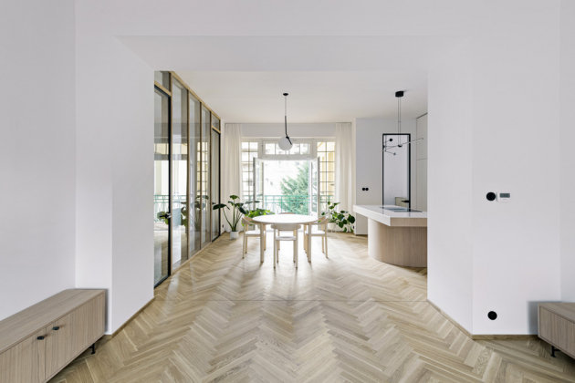 Většinu podlahové plochy 150 m2 kryjí masivní dřevěné vlysové parkety. Vzdušnost prostoru podporuje efektní skleněná stěna s integrovanými dveřmi oddělující chodbu a zádveří. Ze světlého dřevěného masivu je zhotovený i kulatý jídelní stůl s židlemi (Stattmann Furniture). Stejně jako střed obývacího pokoje zdobí centrální bod jídelny závěsné stropní svítidlo (Flos). Moderní, praktický i velmi efektní prvek představuje černobílý mramor použitý v kuchyni. Jeho krásu umocňují drobné černé detaily jako vypínače, úchytky či dřezová baterie.